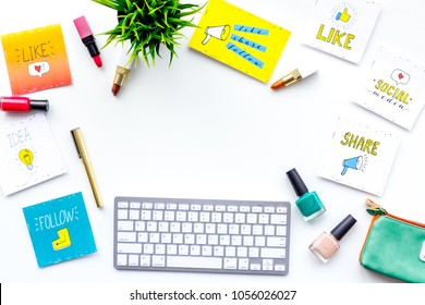 Beauty blogger workplace concept. Keyboard, cosmetics, social media icons on white desk top view space for text