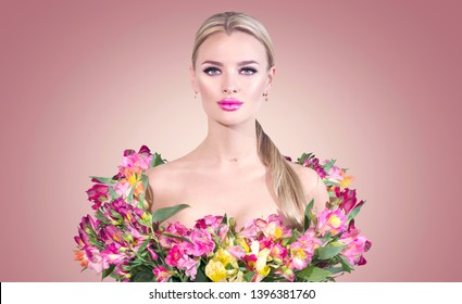 Beauty blonde model girl in summer dress made from colorful fresh flowers. Beautiful spring young romantic woman posing with Alstroemeria flower bouquet over pink color background. Perfect Make-up