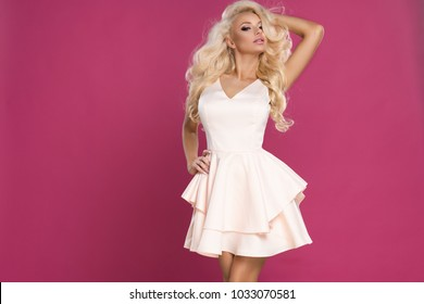 Beauty blonde woman wear pink dress, over pink wall