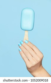 Beauty Blue Manicure. Woman Hand With Nails Art Holding Ice Cream On Blue Background. Close Up Of Female Hands With Fashion French Nails. Art Nail Design. High Quality Image.