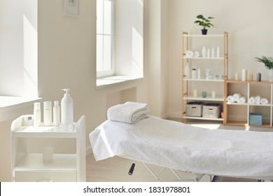 Beauty and body care. Interior of new beauty salon with spa massage table and set of skincare products ready for use. Empty professional dermatologist room waiting for customers