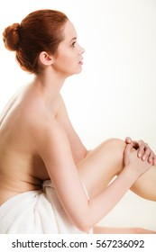 Beauty of body care, showering, clean and fresh skin concept. Naked woman in towel sitting on floor after bathing. Studio shot isolated