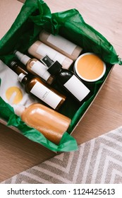 Beauty box with bottles of natural cosmetics, wrapped in green paper. Blogger hair and body care routine, salon treatments