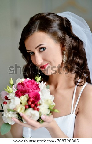b0206fc6ff9 Beauty bride in bridal gown with bouquet and lace veil indoors. Beautiful  model girl in a white wedding dress. Female portrait of cute lady.