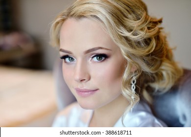 Beauty bride in dressing gown with bridal makeup indoors. Beautiful model girl in colorful wedding robe. Female portrait of cute lady. Woman with hairstyle