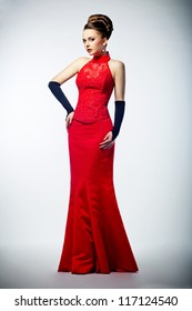 Beauty bride in long bridal red dress and black gloves - studio shot. Formal party