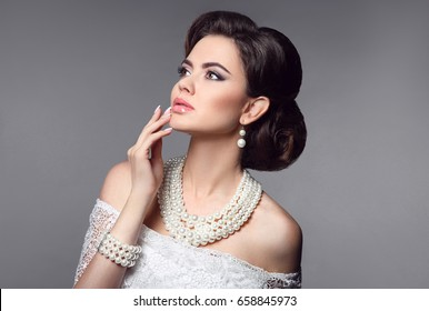 Beauty bride makeup. Elegant fashionable woman portrait. Retro hair style. Brunette model with pearls jewelry women set present isolated on grey studio background.