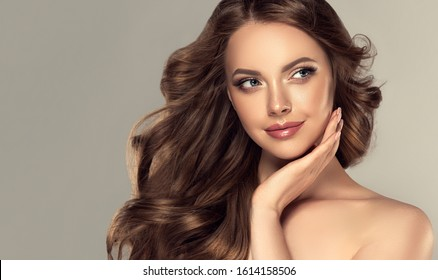 Beauty brunette girl with long  and   shiny wavy black hair .  Beautiful   woman model touching her face with curly hairstyle . - Shutterstock ID 1614158506