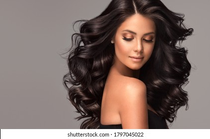 Beauty brunette girl with long  and   shiny wavy black hair .  Beautiful   woman model with curly hairstyle . - Shutterstock ID 1797045022
