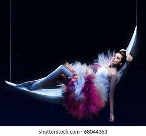 Beauty brunette lying on the crescent moon