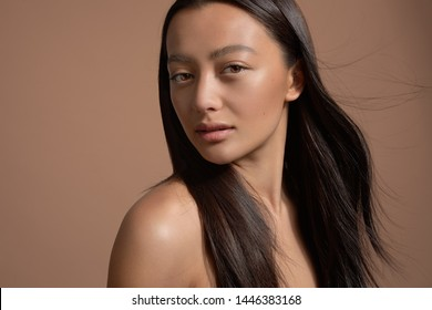 beauty brunette model mixed race model with long strong straight hair blowing. Ideal skin natural makeup on beige background
