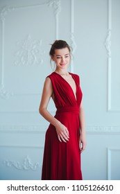 Beauty brunette model woman in evening red dress. Beautiful fashion luxury makeup and hairstyle. Seductive girl silhouette in classic interior.