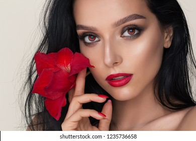 a beauty brunette mystery woman portrait,a red flower in the hands, red vampire eyes