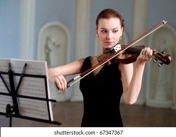 The beauty brunette plays the violin in concert hall