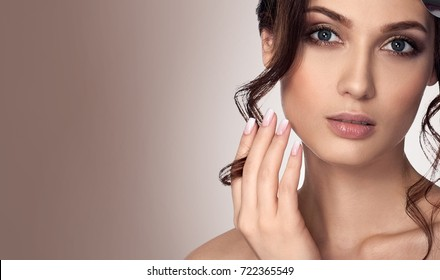 Beauty brunette woman with French manicure, keep the streak of hair on his finger. Grey eyes. fashion large gold rose on the head