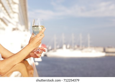Beauty brunette woman standing on the ship,holding glass with white wine and enjoying enjoy the sea view