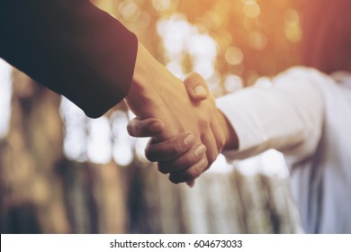 Beauty Business partnership meeting concept. Image business people handshake. Successful businesswomen handshaking after good deal.Blurred background.Cross processing with Sun light