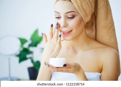 Beauty and Care. Woman with Pure Skin and Towel on the Head Pour Cream on Face. Body Care. Skin Care. High Resolution