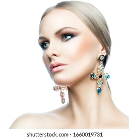 Beauty caucasian model woman face isolated on white background. Bright make-up, clean skin, blonde hair, green eyes. Glamour girl, jewelry earrings. Skincare facial treatment health concept