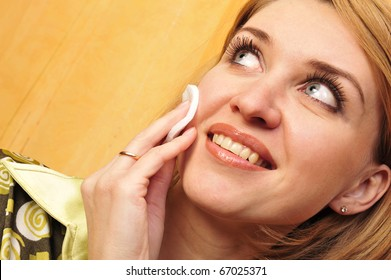 Beauty caucasian young woman applying cosmetic on face