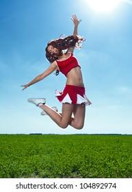 beauty cheerleader on field under blue sky