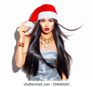 Beauty Christmas fashion model girl with long straight flying hair in red santa hat, beautiful make up, Sexy brunette young woman portrait. Stylish female, fashionable party clothes and accessories.