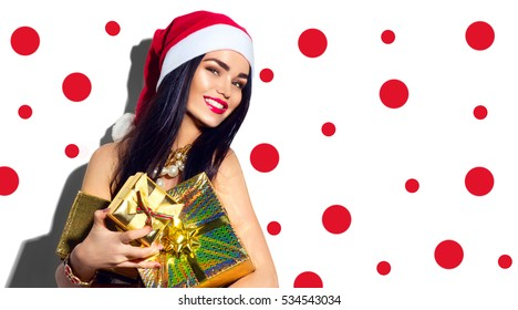 Beauty Christmas fashion model girl with Xmas gift boxes, wearing red santa hat, holding gifts. Sexy brunette young woman portrait. Stylish female, fashionable party clothes and accessories, make up