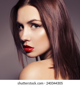 Beauty close up portrait of a brunette woman with red lipstick. Pure skin. Toned image