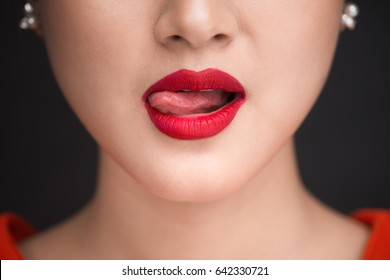 Beauty. Close up view of beautiful woman lips with red matt lipstick licking her desire