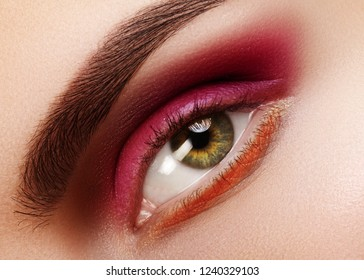 Beauty Close-up of Beautiful Female Eye. Celebrate Fashion Make-up with Red Eyeshadows. Christmas or Valentines Day Makeup. Perfect Eye Brows Shape