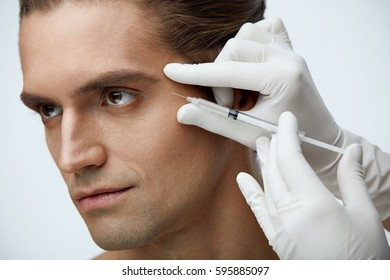 Beauty. Closeup Of Doctor's Hands In Gloves Holding Syringe With Hyaluronic Liquid Near Male Cheekbone. Portrait Of Handsome Man Receiving Cosmetic Face Injection. Facial Treatment. High Resolution