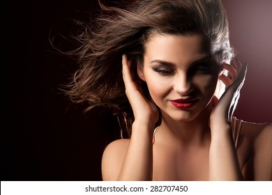 Beauty closeup portrait of attractive elegant brunette woman with red lips and long hair. Perfect makeup. Wind in hair.