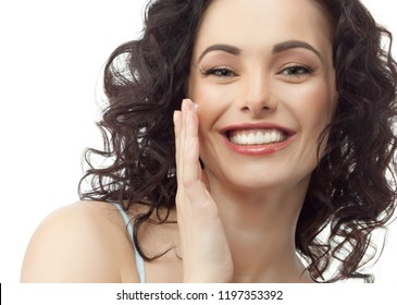 beauty closeup portrait of attractive  young caucasian smiling woman brunette isolated on white studio shot lips toothy smile face hair head and shoulders looking at camera teeth applying cream hand
