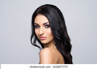 Beauty close-up portrait of beautiful, fresh and healthy woman. Human face over grey background