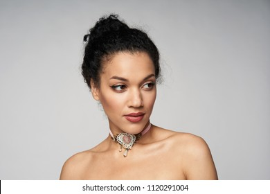 Beauty closeup portrait of beautiful mixed race woman wearing chocker looking to side, isolated on gray background