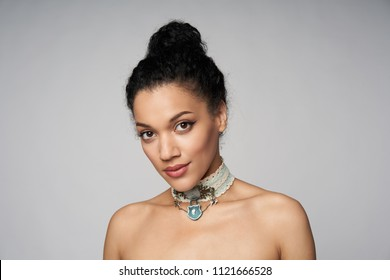 Beauty closeup portrait of beautiful mixed race woman wearing chocker posing, isolated on gray background