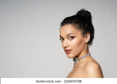 Beauty closeup portrait of beautiful mixed race woman wearing chocker looking at camera, isolated on gray background