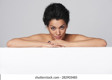 Beauty closeup portrait of beautiful mixed race caucasian - african american woman looking at camera standing behind white banner, isolated on gray background