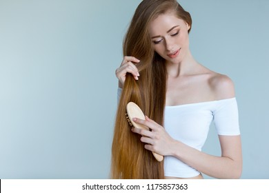 Beauty close-up portrait of beautiful young woman with long brown hair on white background. Hair care concept.