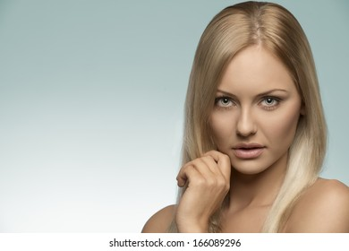 beauty close-up portrait of natural girl with blonde smooth hair, perfect skin and naked shoulder, looking in camera