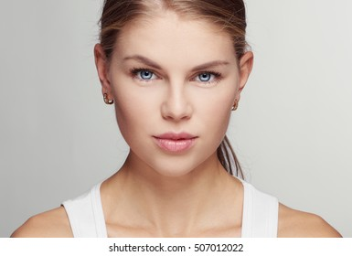 Beauty close-up portrait of young woman with blue eyes and healthy skin. Concept of facial cleansing procedure, skincare and protection.
