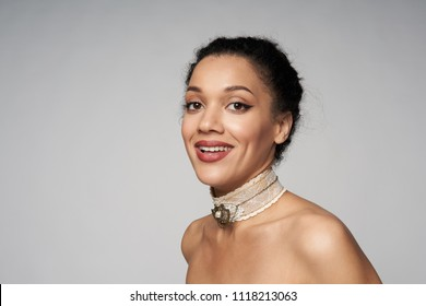 Beauty closeup profile portrait of beautiful mixed race woman wearing chocker looking at camera, isolated on gray background