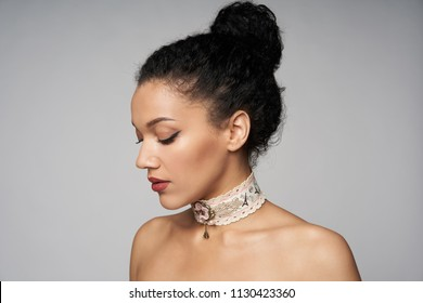 Beauty closeup profile portrait of beautiful mixed race caucasian - african american woman wearing chocker looking down, isolated on gray background
