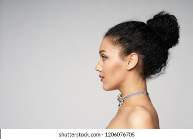 Beauty closeup profile portrait of beautiful mixed race caucasian - african american woman wearing chocker looking forward, isolated on gray background
