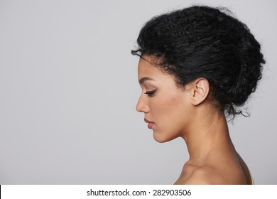 Beauty closeup profile portrait of beautiful mixed race caucasian - african american woman looking forward isolated on gray background