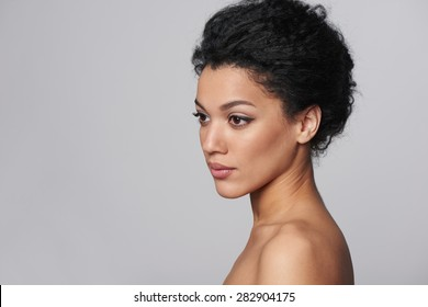 Beauty closeup profile portrait of beautiful mixed race caucasian - african american woman looking out of frame, isolated on gray background