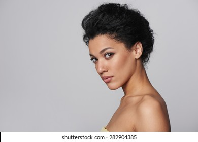 Beauty closeup profile portrait of beautiful mixed race caucasian - african american woman looking at camera, isolated on gray background