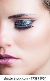 beauty closeup of woman face with glittering eyeshadow studio shot