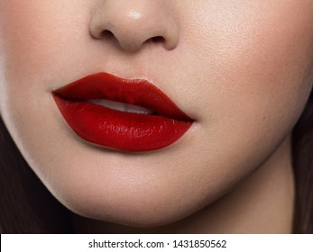 Beauty closeup of women full red lips with shiny skin and long hair. Facial skin care in a spa salon or cosmetology and a fashionable red lip gloss. Evening makeup