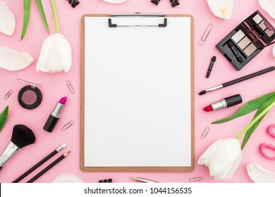 Beauty composition with clipboard, tulips flowers, cosmetics and accessory on pink background. Top view. Flat lay. Home feminine desk.